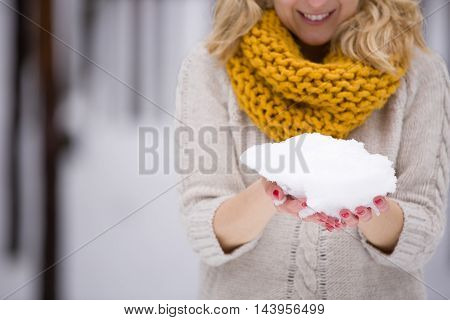 Snow in hands of a young blond woman with red manicure warm sweater and yellow scarf. Winter walks outdoors. Snow in the forest.