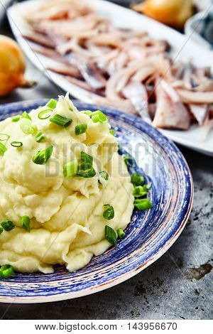 Close up shot of mashed potatoes with chopped green onion and herring fillets with pickled onions. Perfect matching of garnish on metal background, kitchen towel, fresh onions, jar of pickled onions