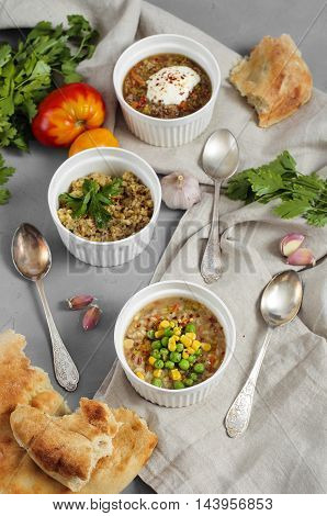 Three Bowls Of Bean, Quinoa Soup And Mushroom Bulgur On A Gray Background.