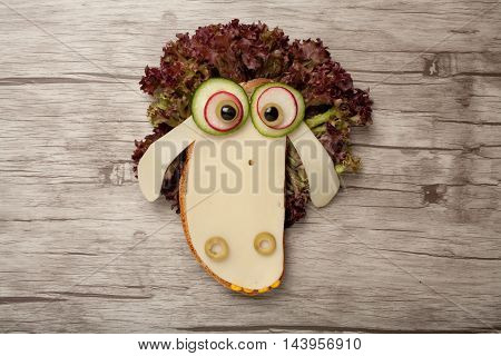 Confused sheep made of cheese and bread on wooden background