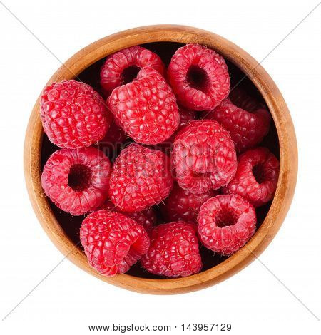 Raspberries in a wooden bowl on white background. Red ripe berries of Rubus species. Edible fruits, raw, organic and vegan food. Isolated macro photo close up from above.