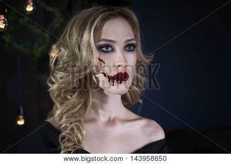Beautiful young blonde woman in black dress with halloween make up and bloody face art victim of domestic violence close up portrait