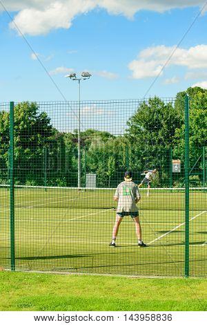 GLASGOW SCOTLAND - JULY 21 2016: Two men playing tennis at the Kelvingrove Lawn Bowls and Tennis Centre in central Glasgow.