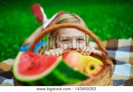 happy child with a fruit basket outdoor in the summer park