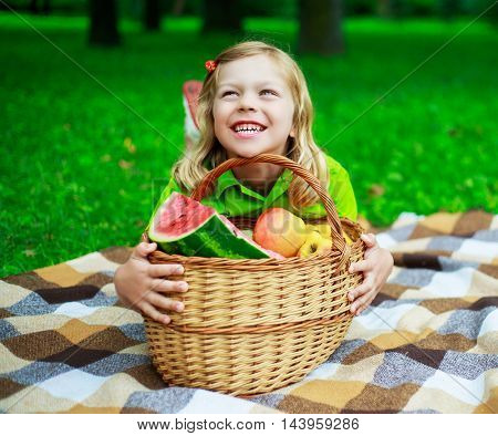 happy child with a fruit basket outdoor in the park