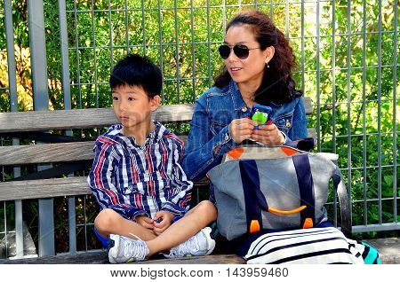 New York City - July 29 2013: Asian mother and her son relaxing on a park bench at Pier 84 on the Hudson Rive
