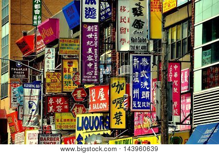 New York City - August 16. 2011: Colourful signs in both Chinese characters and English cover storefronts in NYC's largest Chinatown located in Flushing in the Borough of Queens
