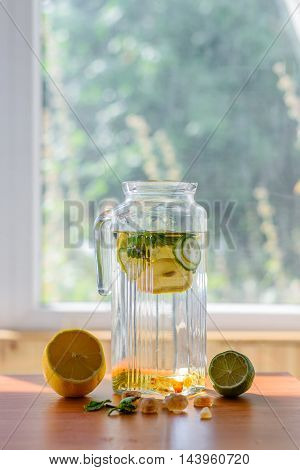 Pitcher of homemade lemonade with ingredients on window background. Refreshing in the heat. Copyspace.
