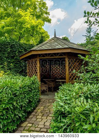 Wooden summer house surrounded by green shrubs and trees