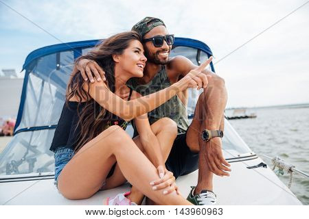 Beautiful young couple hugging and pointing away on boat
