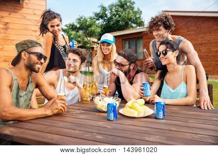Portrait of cheerful young friends laughing and having party at the table outdoors