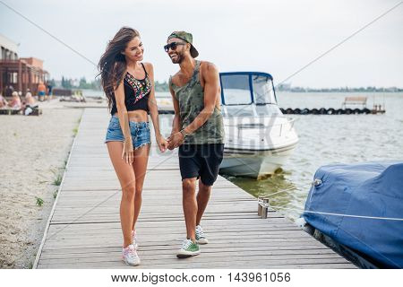 Happy young couple in love walking at the wooden sea pier