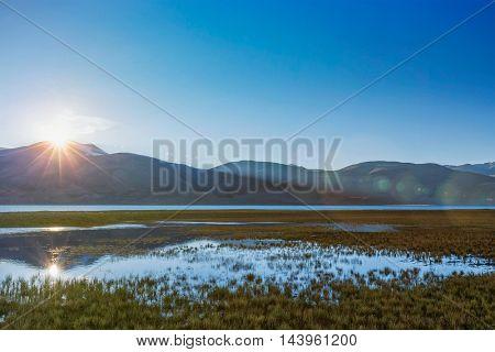 Lake Tso Moriri in Himalayas on sunrise. Ladakh, Inda. With lens flare
