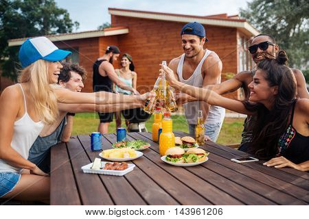 Happy group of young cheerful friends having fun at picnic outdoors