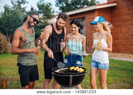 Group of smiling young people drinking beer and cooking on barbeque grill outdoors