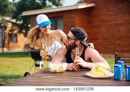 Happy young couple sitting and drinking beer outdoors together