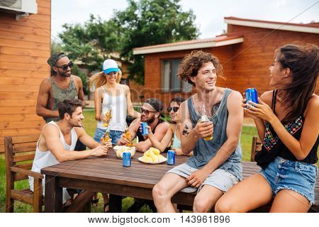 Cheerful young couple drinking beer and soda with friends on outdoor summer party