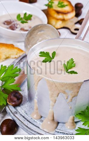 Cream soup of pureed chestnuts on a concrete background. Selective focus.