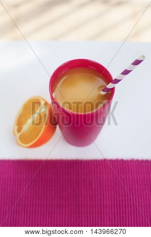 Colorful magenta glass with orange juice on a white table outside in a summer day.