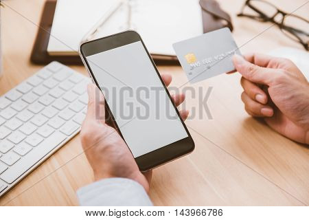 Online paymentMan's hands holding a credit card and using smart phone for online shopping