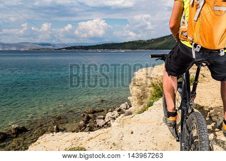 Mountain biker riding on bike at the sea and summer mountains. Man rider cycling MTB on country road or single track. Sport fitness motivation inspiration in beautiful inspirational landscape view.