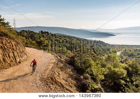 Mountain biker riding on bike in autumn inspirational mountains landscape. Man cycling biking on dirt road trail track. Sport fitness motivation and inspiration outdoors MTB rider training Croatia.