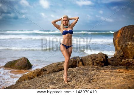 Beautiful woman in the blue bikini posing on the lonely rock in the ocean on the storm background.