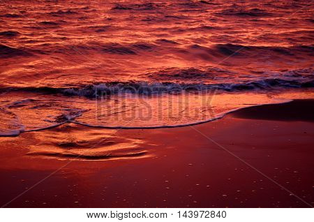Sea waves during a colorful sunset over a beautiful and romantic beach