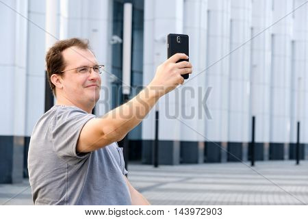 Middle age man making selfie outdoors