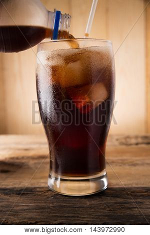Pouring of cola Cold fizzy cola soda with ice in glass cup