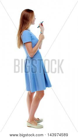 back view of writing beautiful woman. Young girl in dress. Rear view people collection.  backside view of person. Isolated over white background. Skinny girl in a blue dress and pen writes on the