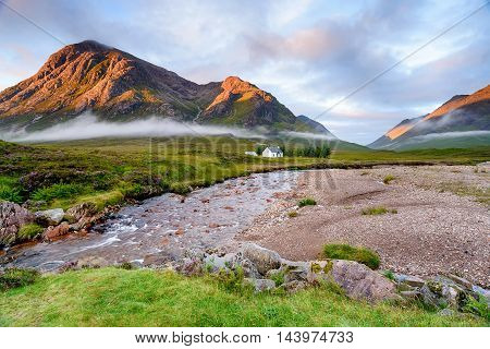 A beautiful cottage on the banks of the river Coupall and backed by the Buachaille Etive Mor mountains at Glencoe in Scotland