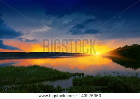 orange sunset over river. Dramatic sky. Twilight