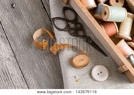 Wooden box with a spools of thread, scissors, measuring tape, button and needles on gray fabric on a wooden table.