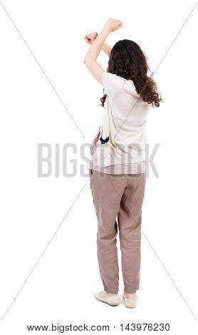 back view of dancing young beautiful  woman. girl  watching. Rear view people collection.  backside view of person.  Isolated over white background. Long-haired curly girl gesturing with his hands.