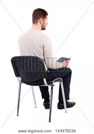 back view of man sitting on chair and looks at the screen of the tablet.  businessman watching. Rear view people collection.  backside view of person.  Isolated over white background. The bearded man