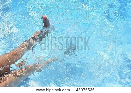 Children's feet in the water.  Background for summer holiday, traveling and vacation.