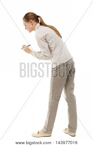 back view of writing beautiful woman. Rear view people collection.  backside view of person. Isolated over white background. Skinny girl in white denim suit writing pens.
