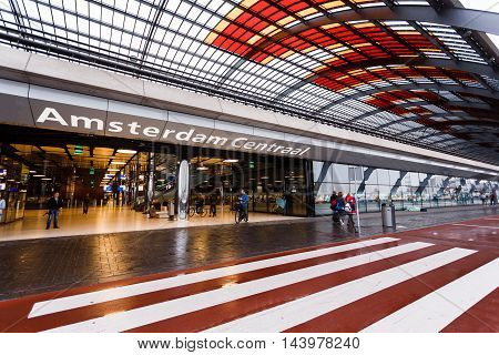 Amsterdam Netherlands - July 01 2016: Some people expect transport in the railway station rainy weather