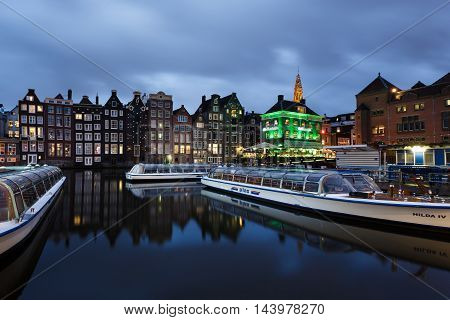 Amsterdam Netherlands - July 01 2016: Tourist boats in the marina on the background of traditional Dutch houses evening time