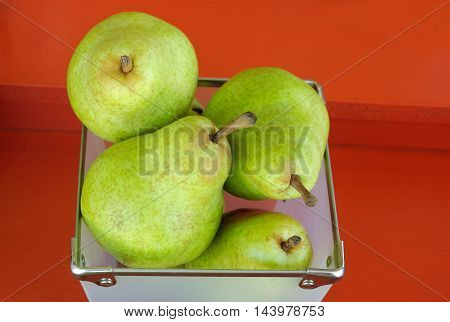 pears fruits in a basket on red background