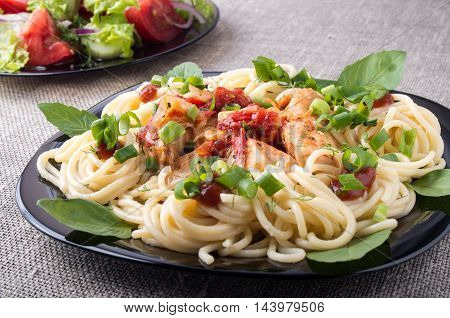 Homemade meals on a gray mat - pasta with pieces of stewed chicken and vegetable salad with tomato and lettuce