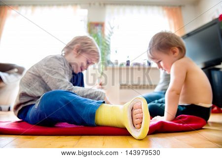Two Little Boys Sitting On The Floor Playing.