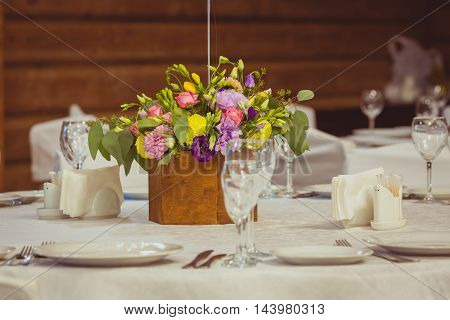 flower composition in wooden vase on the served table in the restaurant. Wedding dinner
