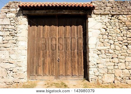 old big wooden doors closed the wall around is built with stones