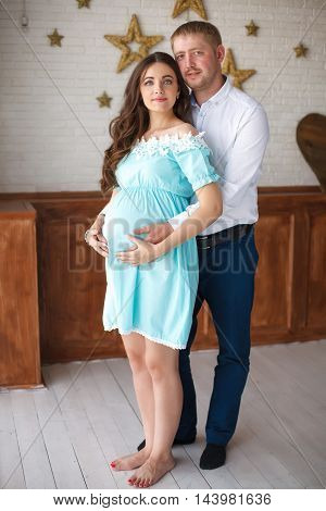 Young pregnant woman and her husband touching belly with hands