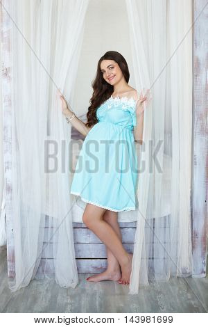 Young pregnant woman standing near bed in studio