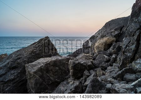 Quiet evening sea cliffs rocks and sky with different tones