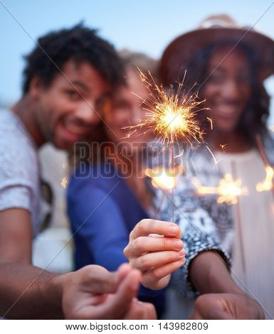 Four young casual friends having fun with sparkling lights at an urban celebration with a cityscape view in the evening