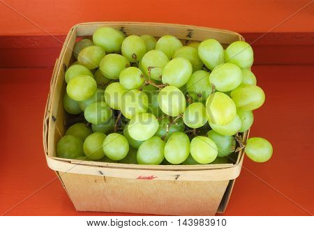 green grapes in wood basket on red background